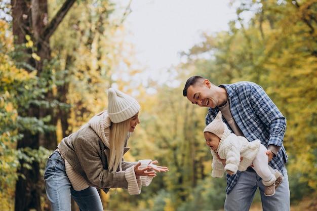 秋の公園で小さな娘と若い家族