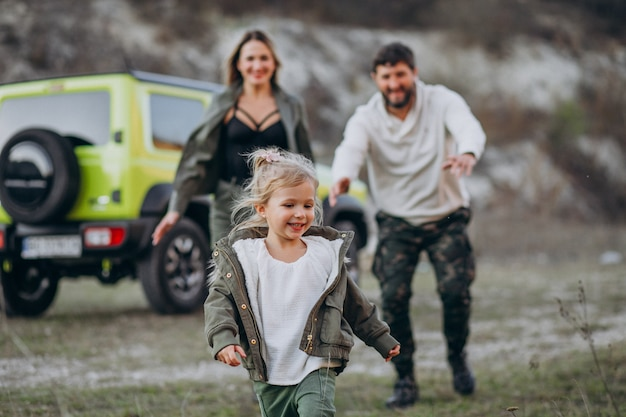 Young family with little daughter stopped in forest