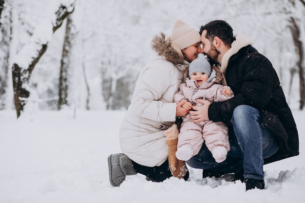 Young family with little daughter in a winter forest full of snow