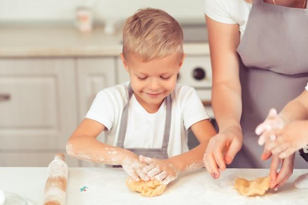 小さな子供と赤ちゃんの息子が家でジンジャーブレッドクッキーを作っている若い家族。