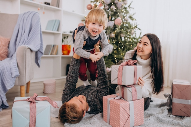 Young family with little son by christmas tree