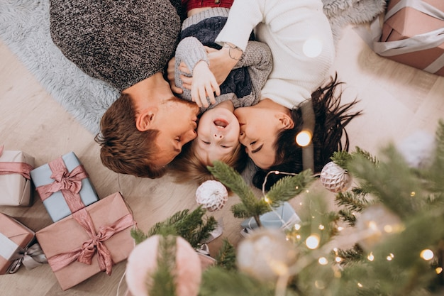 Young family with little son under the christmas tree