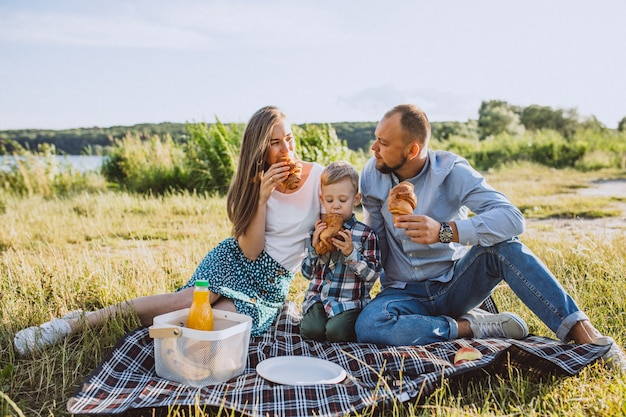 Молодая семья с маленьким сыном, пикник в парке