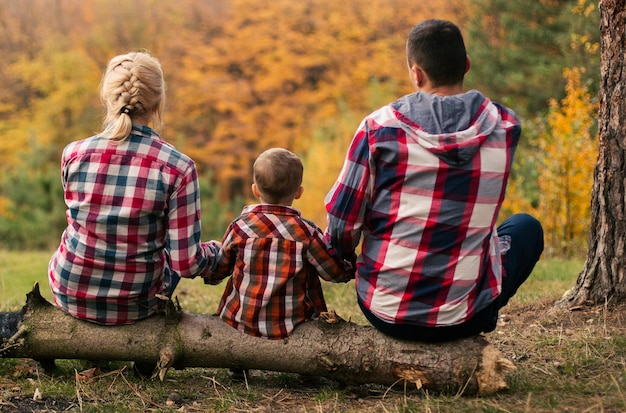 Young family with little son spend time in forest