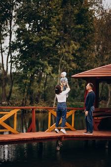 川沿いの橋の上を歩く幼い息子と若い家族