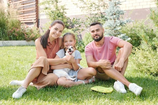 笑顔で芝生の上に座って裏庭で彼らの小さな犬と一緒に時間を過ごす1人の娘を持つ若い家族