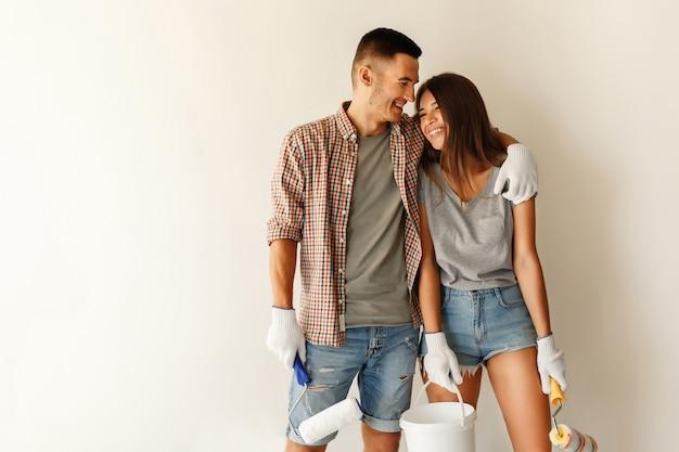 Молодая семья с краской валик обнимает и улыбается после покраски стен в новом доме