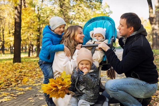 公園で小さな子供を持つ若い家族。幸せな笑顔の両親。愛と優しさ。黄金の秋の季節。