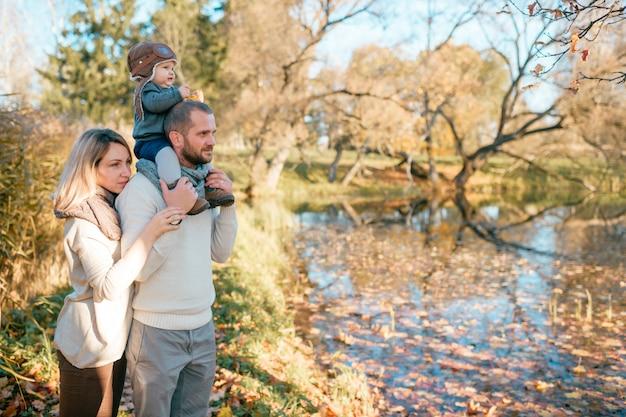 Молодая семья с ребенком на плечах отцов, стоя возле озера осенью.