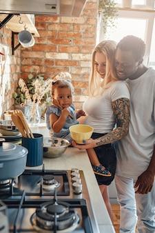 日光の下で居心地の良いキッチンで娘と若い家族
