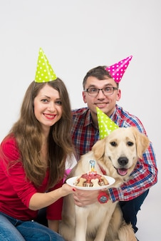 犬のゴールデンレトリバーを持つ若い家族は、1歳の誕生日を祝います。