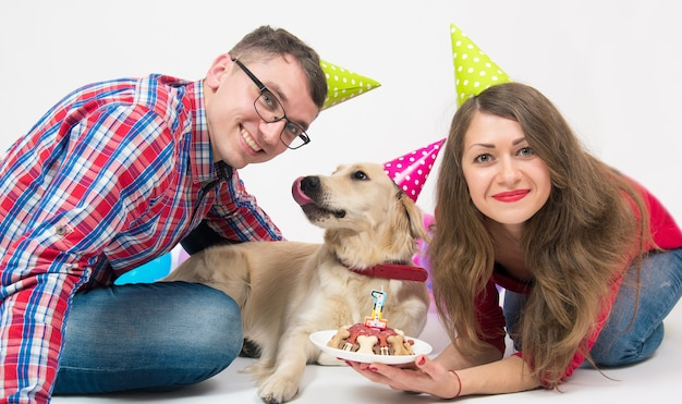 Молодая семья со своей собакой золотистого ретривера отмечает годовщину рождения.
