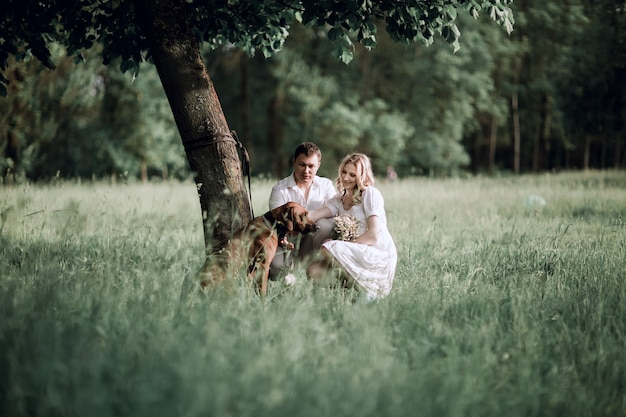 Young family with their dog on the lawn in the park