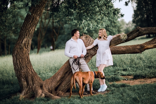 Young family with their dog standing near a big tree
