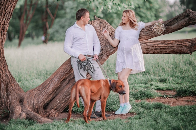 Young family with their dog standing near a big tree.