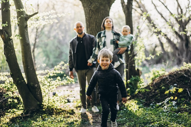Young family with their kids having fun in the forest