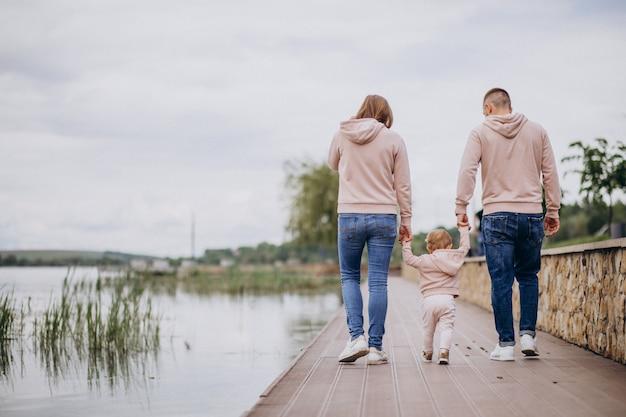 Молодая семья с маленьким ребенком в парке у озера