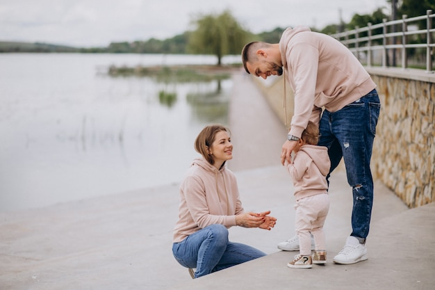 Young family with their little baby child in park by the lake