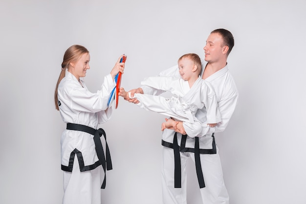 Young family with their little boy practicing martial arts on white