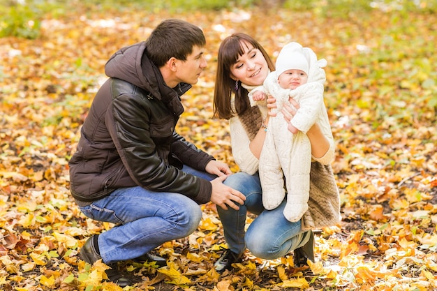 Молодая семья с новорожденным ребенком проводит время на открытом воздухе в осеннем парке.