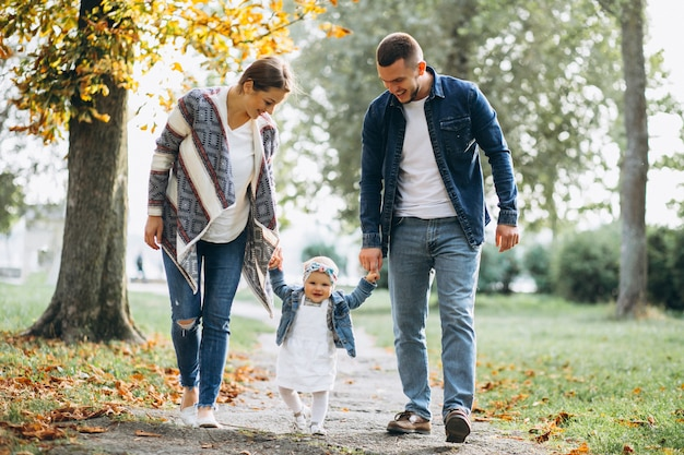 Young family with their small daughter in autumn park