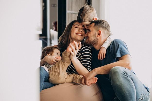 Молодая семья с сыновьями дома с удовольствием