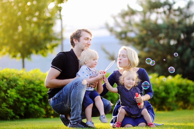 Young family with their toddler children blowing soap bubbles outdoors on sunny summer day