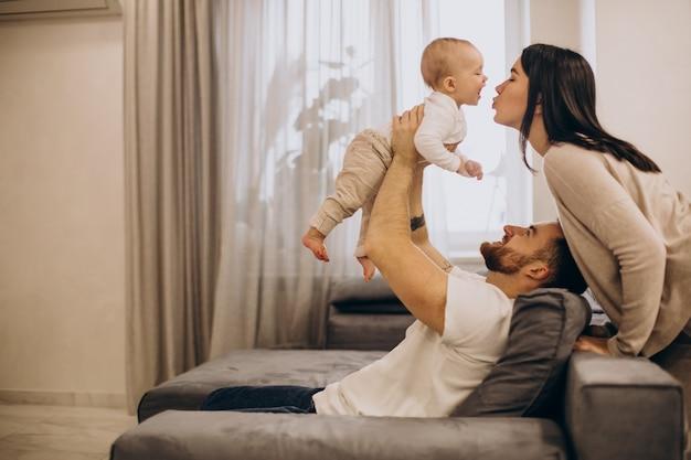 Молодая семья с маленькой дочкой сидит на тренере дома