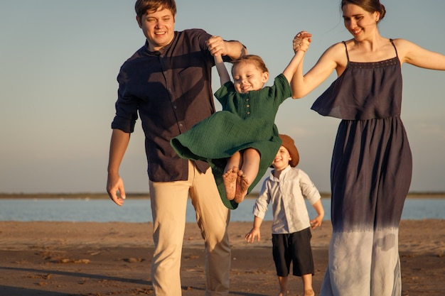 저녁 해변에서 노는 두 아이와 젊은 가족.