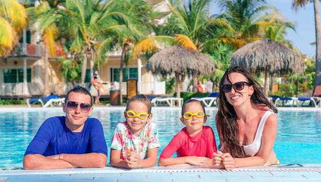 두 아이를 가진 젊은 가족은 야외 수영장에서 여름 휴가를 즐길 수
