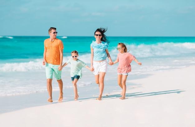 Молодая семья с двумя детьми на пляжном отдыхе