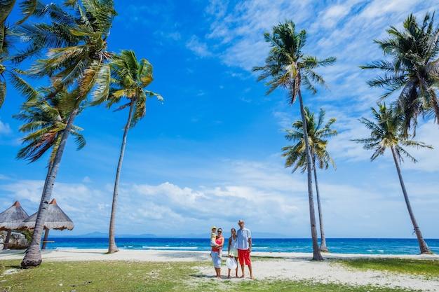 Молодая семья с двумя детьми гуляет на тропическом пляже