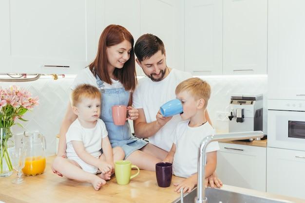 美しい白いキッチンで朝食をとっている2人の小さな子供を持つ若い家族