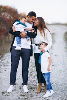 Молодая семья с двумя сыновьями вместе за пределами парка