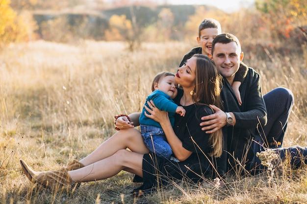 一緒に公園に座っている2人の息子を持つ若い家族