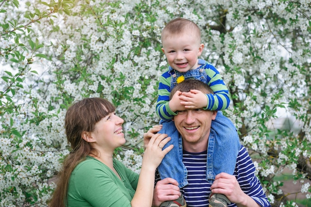 Young family with young son in a blossoming spring garden