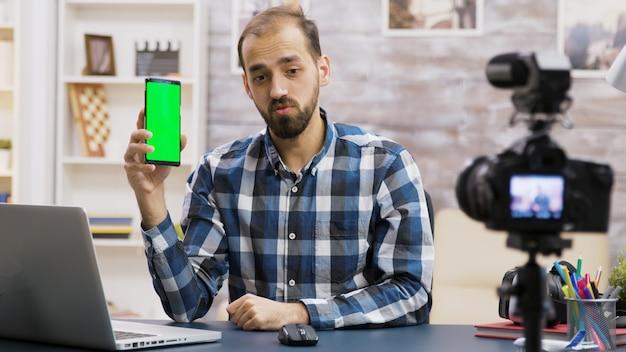 Giovane e famosa influencer che filma la recensione di un telefono con schermo verde. creatore di contenuti creativi.