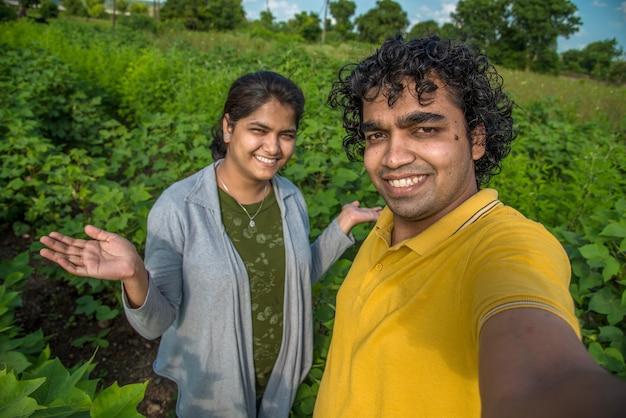 목화 농장에서 스마트 폰 또는 카메라로 셀카를 복용하는 젊은 농부 부부.