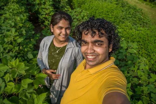 Young farmer couple taking a selfie with a smartphone or camera in the cotton farm.