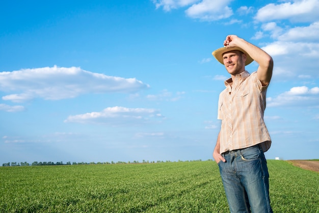 Young farmer in the field observing crops