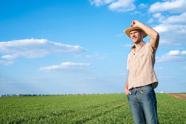 Giovane agricoltore nel campo osservando i raccolti