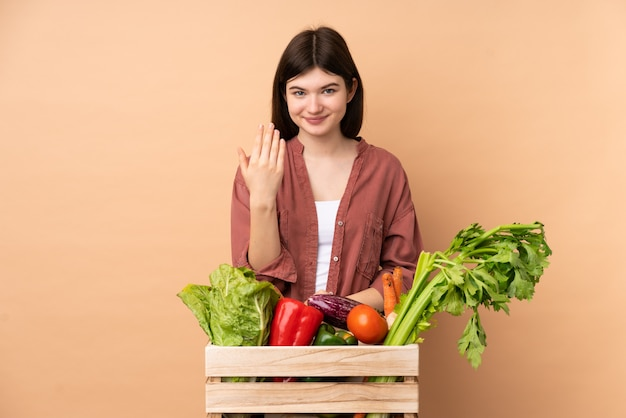 Young farmer girl with freshly picked vegetables in a box inviting to come with hand