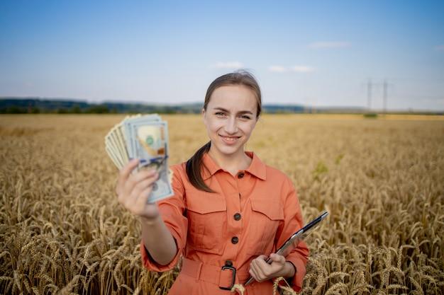 Молодой фермер держит доллары в золотом пшеничном поле