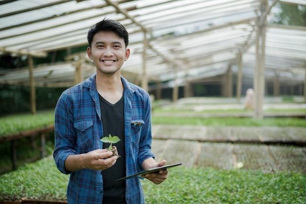 카메라 디지털 농업 사진 개념을 보고 종자 식물과 태블릿을 들고 젊은 농부