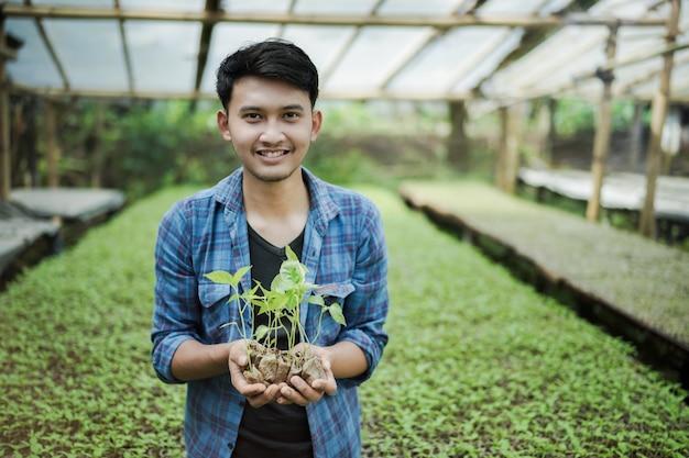 농장 스마트 농업 사진 개념에서 종자 식물을 들고 젊은 농부