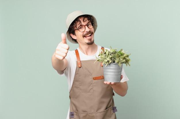親指を立てて前向きに笑って、誇りを感じている若い農夫の男