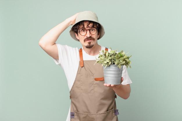 Молодой фермер чувствует стресс, тревогу или испуг, с руками за голову