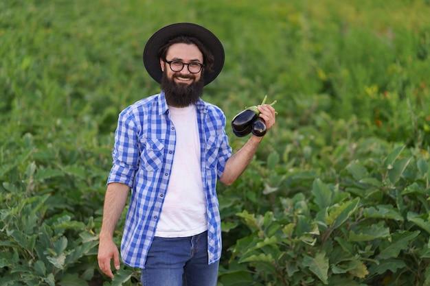 젊은 농부 남자는 그의 정원에서 막 따온 짙은 파란색 가지가 달린 앞치마를 손에 들고 있습니다. 농업, 유기농 제품, 깨끗한 식사, 생태적 생산의 개념. 확대