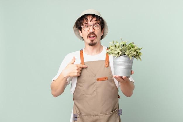 자신을 가리키는 입을 크게 벌리고 놀란 듯 놀란 젊은 농부 남자