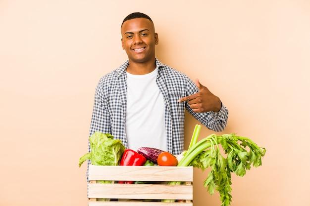 自信を持って自信を持ってシャツの空白スペースを手で指しているベージュの壁人の若い農夫男